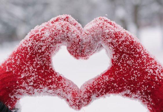 قلب برفی با دست در هوای برفی و سرد