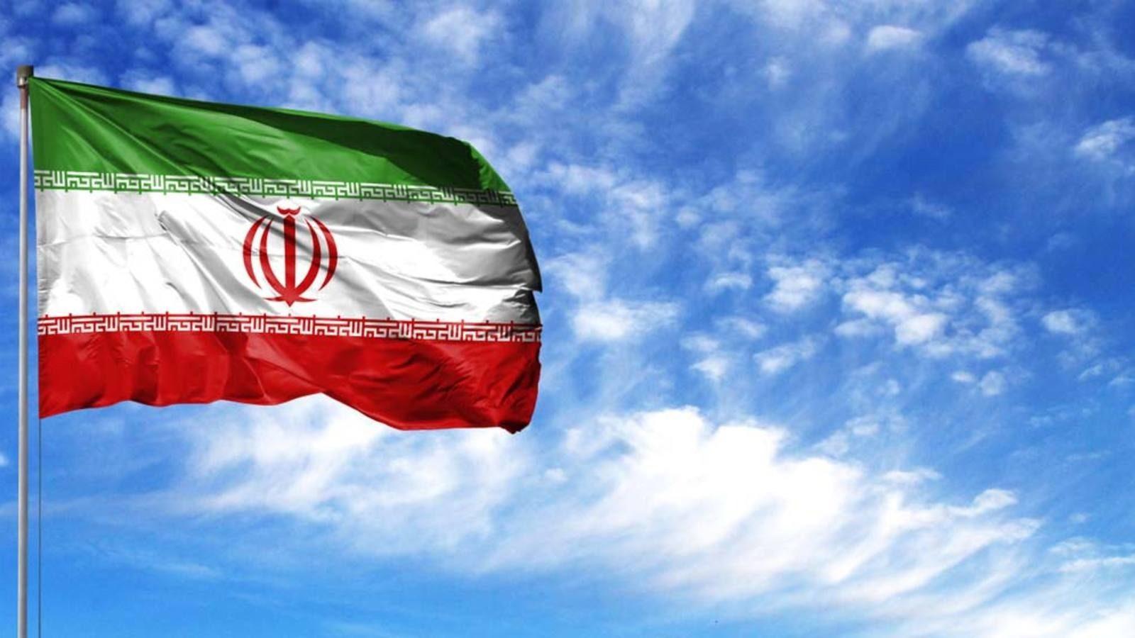 عکس پرچم ایران در حال حرکت در آسمان آبی و ابر